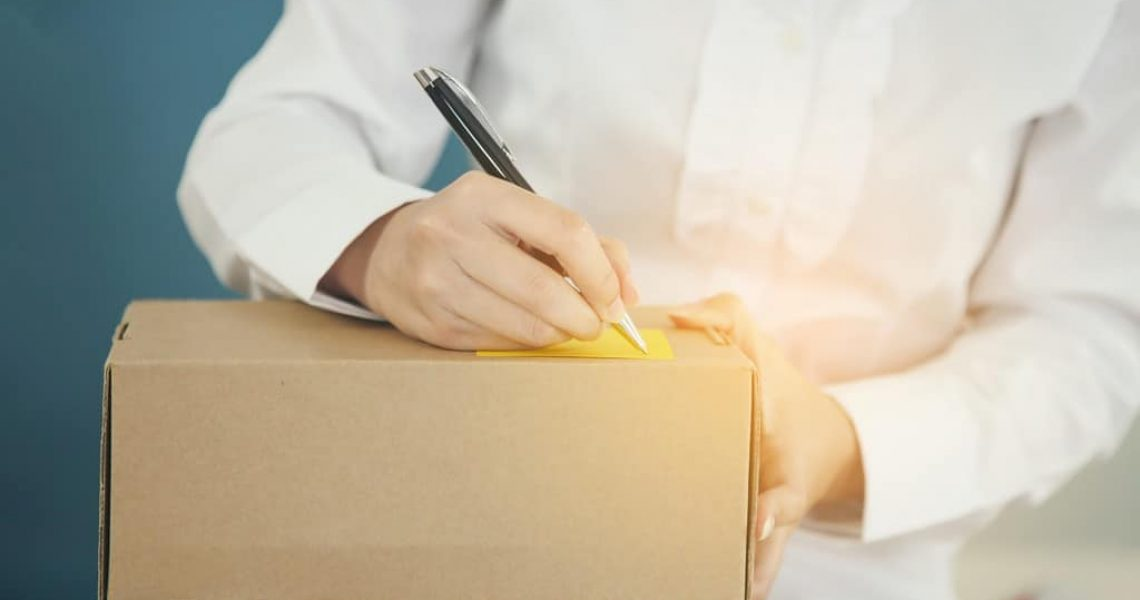Delivery Concept, Young Asian woman working online shopping at home office.Young woman writing note on parcel at warehouse, closeup.