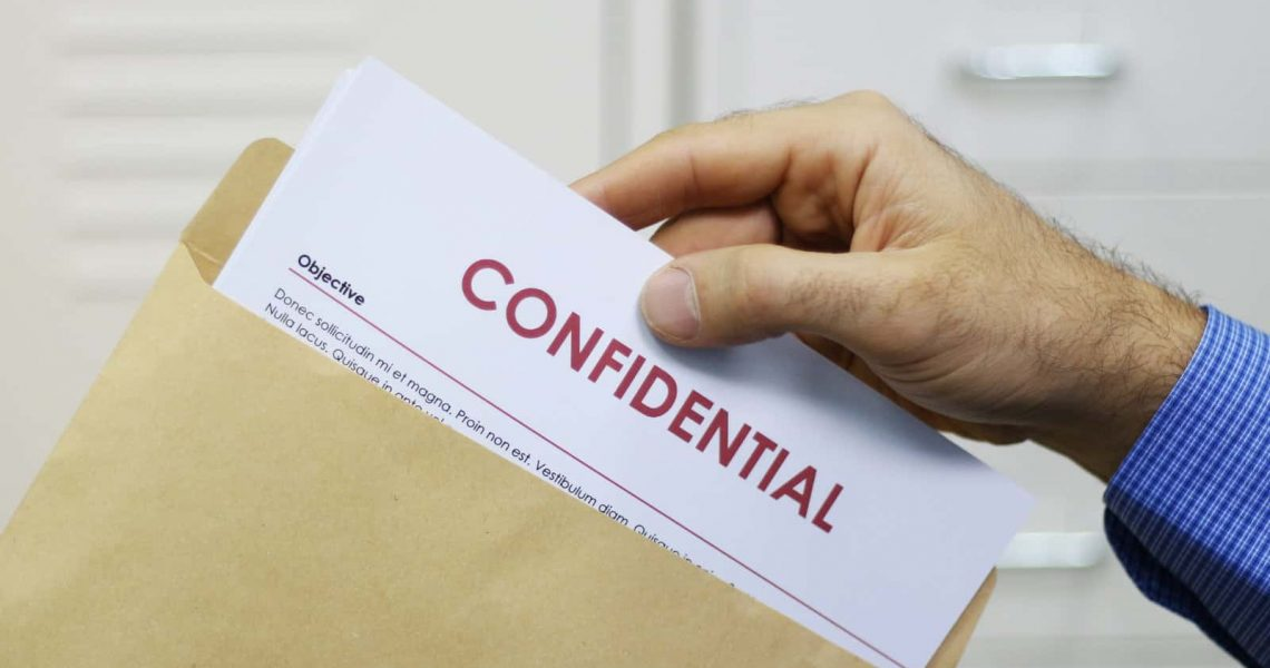 Cropped view image of a man handling confidential documents placing them inside a brown manilla envelope for mailing